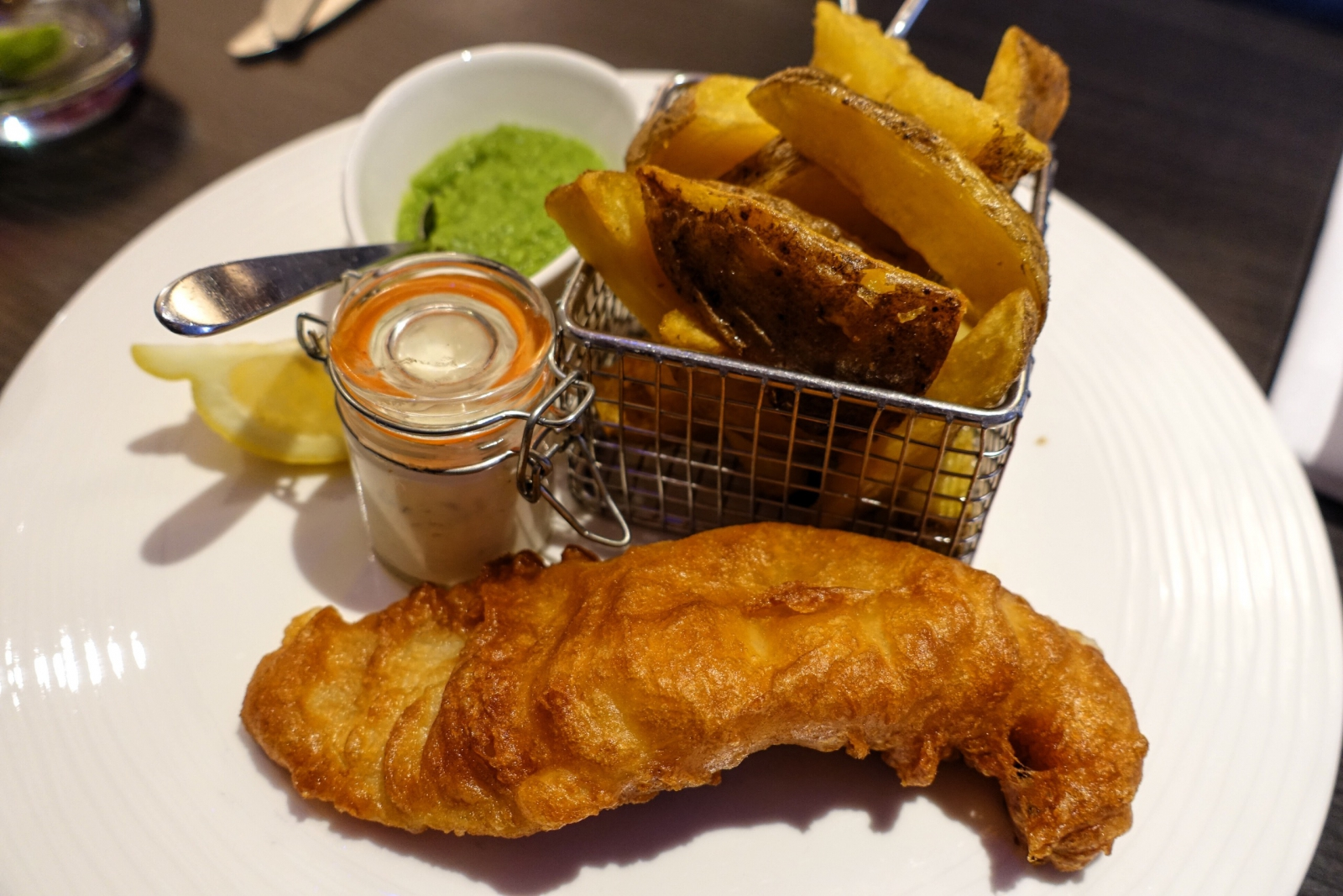 Beer-battered fish and chips with tartar sauce and mushy peas at Brigade in London